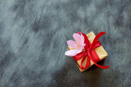 box in festive packing with a red bow and lilac flower on a dark chalky surface top view  gift with tender feelings