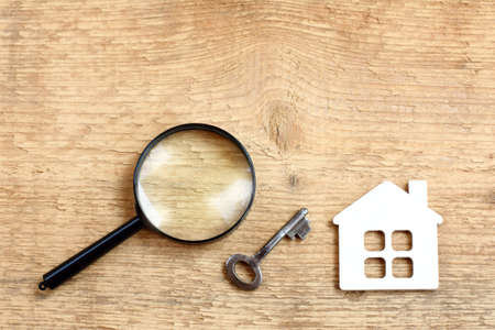 flat layout with a house, key and magnifying glass on a wooden surface top view  selection of retro real estate Stock Photo