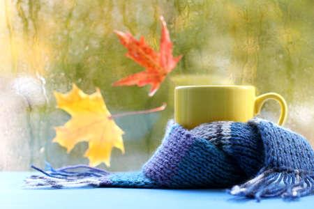 葉のメープルと濡れている窓の背景に青のスカーフで黄色のマグカップ秋雰囲気を温暖化