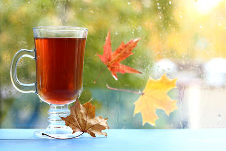tea in a transparent mug on the background of a window with drops and stuck leaves after the rain autumn maple drink