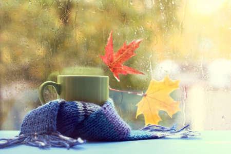 メープルと濡れている窓の背景に青のスカーフ グリーン マグカップ葉ホットド リンク秋スタイルで