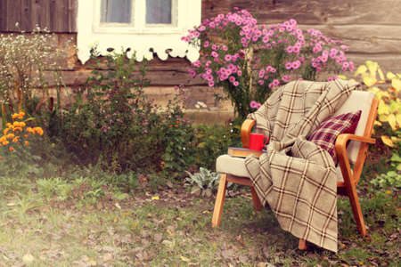old chair with blanket, book and red mug stands in the garden near village house  comfortable place to rest Stock Photo