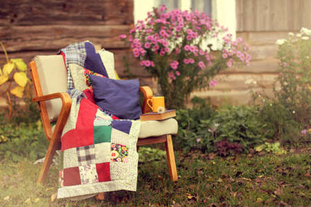 old chair with a blanket, a book and a yellow mug stands in the garden near the wooden house  cozy autumn weekend