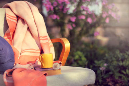 Armchair  with  blanket, pillow, book and cup on the background of  flower bed in the garden  warming atmosphere for relaxation