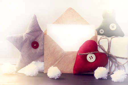 Soft heart with gift and a star next to an open letter in an envelope on the table  congratulations on the holiday