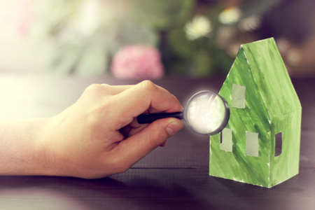 hand with a magnifying glass and paper layout of green houses  environmental materials in construction
