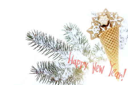 waffle horn filled with figured cookies against the background of snow-covered  branches of a Christmas tree  greeting card happy new year