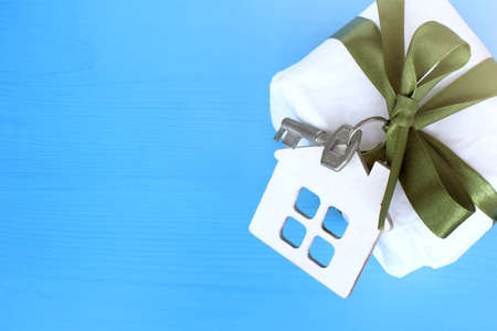 layout houses with key tied with green bow to gift on blue wooden background top view  complete refurbishment as gift