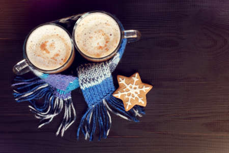 two glass mugs with frothy cappuccino, in a blue scarf and gingerbread cookie view from the top  warming the coffeehouse for winter weekend