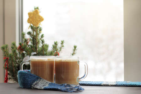 two glass glasses with frothy cappuccino on the background of festive Christmas tree by the window  winter coffee break