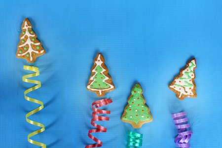 decorated ginger cookies in the form of Christmas trees fly upwards on serpentine ribbons on a blue background  abstract festive salute