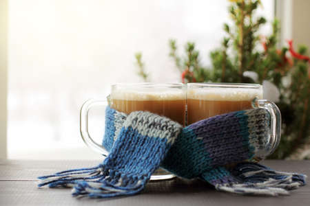 Two mugs with frothy cappuccino in a blue scarf on the background of a festive Christmas tree by the window  together we meet the winter morning