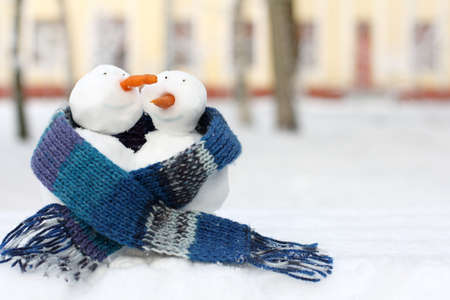 Couple of happy snowmen in blue scarf walking together in winter / warming date of lovers