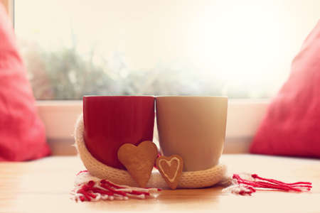 two mugs wrapped in scarf next to pair of cookies in the shape of heart on table in front of window  together in cozy atmosphere Stock Photo