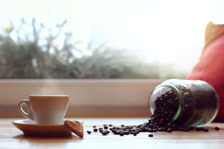 white mug on the background of coffee beans scattered from can on the table by the window  favorite warming drink