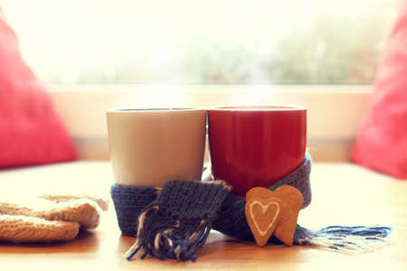 White and red mug wrapped in a blue scarf and two cookies in the form of hearts in the background of the window  warming drinks for joint pastime