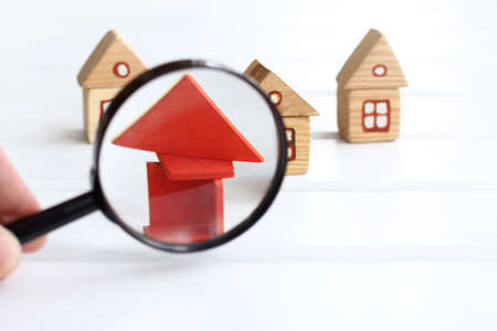 red elements of the house at study with magnifying glass / careful revealing of hidden defects of construction