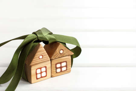 pair of wooden houses together tied with a green bow  gift offer two for the price of one