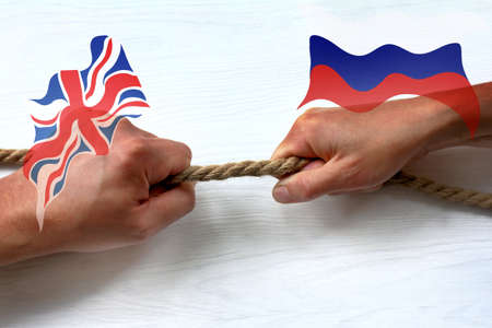 flags of England and Russia against the background of two hands pulling the rope in different directions conflict between states