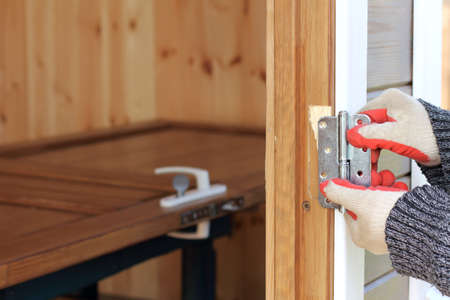 The carpenter is trying on new hinges for installing door in wooden house / adjusting to the size of a building Banque d'images - 102846952