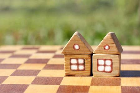 Zwei kleine Holzhaus auf einem Schachbrett / Grundstück zum gemeinsamen Spielen im Leben