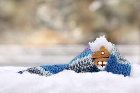 kleines Holzhaus in einem warmen blauen Schal mit Schnee bedeckt / Sachversicherung gegen Naturphänomene Standard-Bild