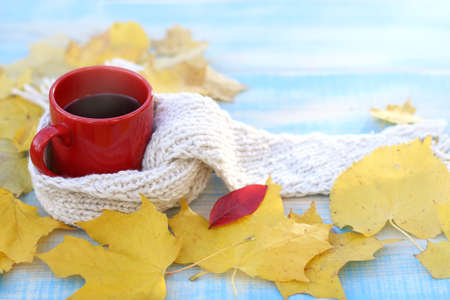 red mug with a hot drink in a bright scarf with yellow autumn leaves on the table / still life with warming coffee