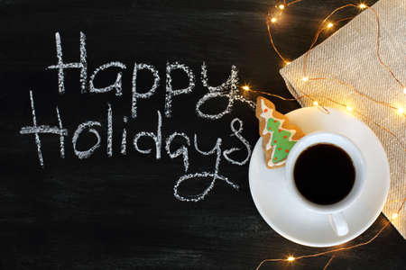 cup of black coffee, ginger biscuits and blanket with garland / happy holidays with a warming mood