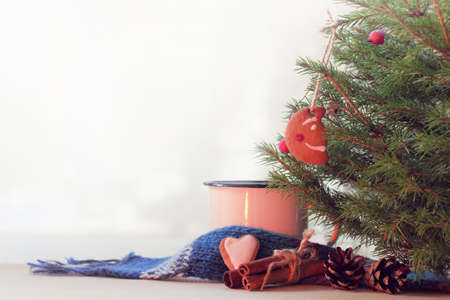 mug with a scarf and biscuits stands on the table under the Christmas tree  warming atmosphere of winter holidays Stock Photo
