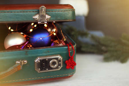 Christmas-tree decorations are visible in ajar retro suitcase / preparing for the winter holidays