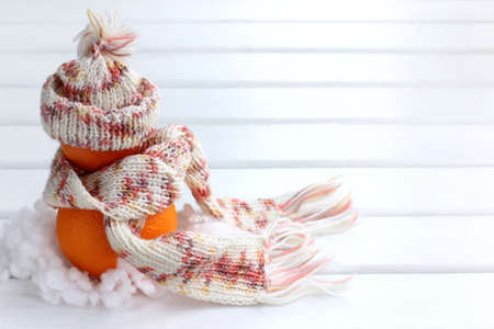 two orange mandarin in a hat and scarf on a light surface / fruit snowman