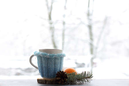 mandarin mug decorated with fir branch and cone on table against the background of window in winter.fragrant warming drink