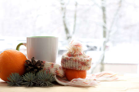 cup in a scarf and a mandarin in a hat decorated with a fir branch and a cone against the window. morning warming drink in winter Banque d'images
