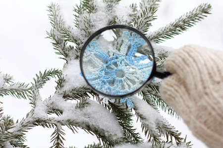 the hand-knotted snowflake is visible in a magnifying lens against a winter landscape  magical Christmas transformation