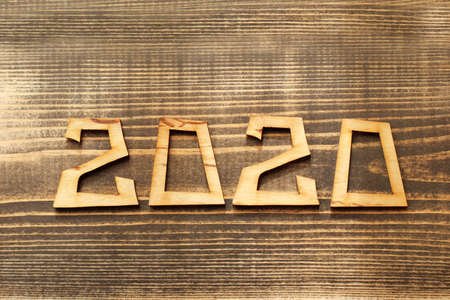The number denoting the year cut from plywood lies on a wooden surface top view. natural background 2020