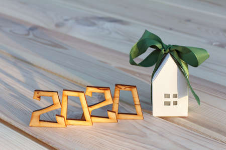 house in gift box next to a wooden number indicating the year. ecological real estate in 2020