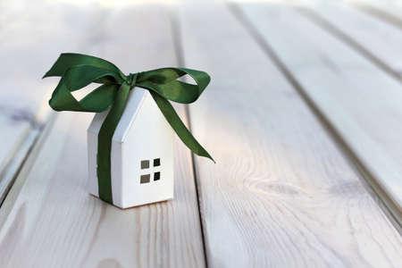 Layout della casa di carta bianca avvolto in un nastro verde con fiocco. piccolo regalo grande vacanza Archivio Fotografico
