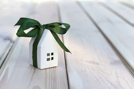 White paper house layout wrapped in green ribbon with bow. small gift great holiday