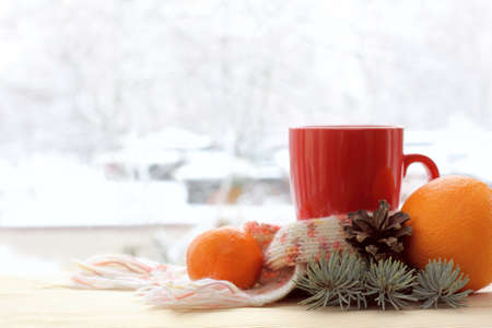 mug with a scarf, spruce branch, pine cone, orange, mandarin on a table by the window with a winter landscape. Christmas still life Banque d'images