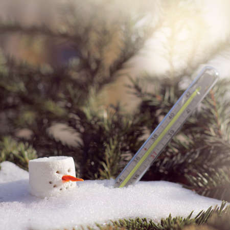melting snowman under and a thermometer in a snowdrift under the sun in spring. oncoming of spring