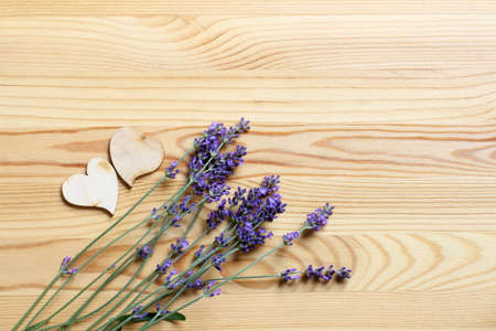 two wooden hearts with with a bouquet of lavender on a wooden surface top view. fragrant romantic background