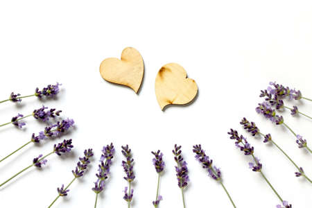 two wooden hearts with with lavender branches on a light surface top view. fragrant romantic valentine Reklamní fotografie