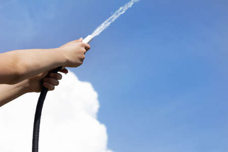 watering hose in the hands of a gardener splashes out a stream of water against a blue sky. life-giving moisture for growth