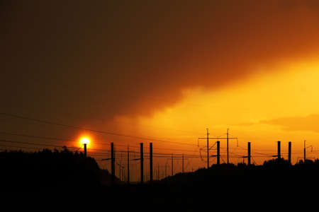 Silhouettes of wires of a high voltage power line against the backdrop of enchanting evening sunset. unusual urban landscape