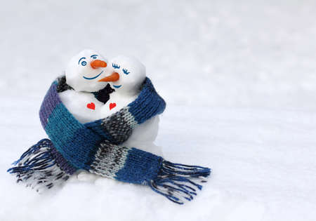pair of snowmen together covered with a large knitted scarf. love warms when you are together Reklamní fotografie