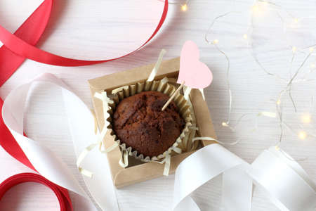 chocolate muffin with valentine on the table with ribbons and garland lights. sweet holiday of lovers Reklamní fotografie