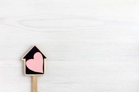 Layout of a house on a stick with a heart symbol on a light wooden background.  home sweetheart concept Reklamní fotografie