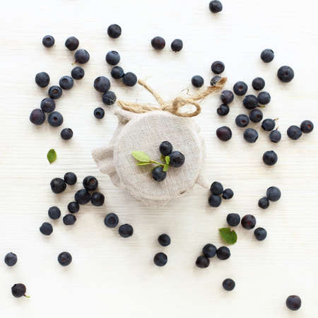 jar with a fabric lid decorated with fresh blueberries top view. natural ingredients for jam