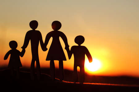 silhouette of a married couple with children, against the backdrop of the sunset in the evening. spending time together is beautiful