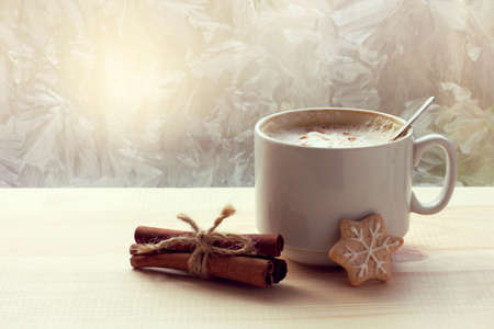 cup with coffee, cinnamon and cookies on the background of a window with frosty patterns. winter morning with coffee